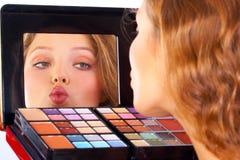 Make up. Pretty woman applying make up royalty free stock photo