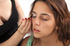Make up. Artist doing professional  of young woman stock images