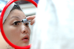 Make-up. Chinese girl touching up her eye lashes Stock Images