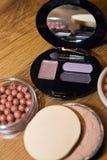 Make-up. Multi-colored eyeshadows on wood background Royalty Free Stock Images