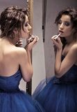 Make up. Pretty brunette doing make up looking at the mirror - vintage look royalty free stock photography