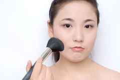 Make-up. Beautiful girl applying make-up with a brush Royalty Free Stock Photography