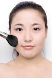 Make-up. Beautiful girl applying make-up with a brush Royalty Free Stock Image