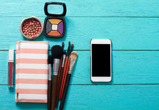 Make up accessories. Top view. Blue wooden background. Cellphone with blank screen. Cosmetic products Stock Images