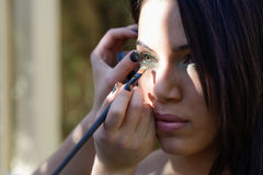 Make-up applying eyeshadow on model's eye Stock Photography
