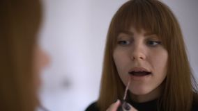 Make up applying, lipgloss, lipstick. Portrait of young attractive red-haired girl rouging her lips, close-up. Beauty woman Make-u stock footage