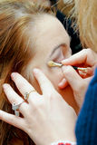Make-up artist. Applying eye-shadow on model eye royalty free stock photo