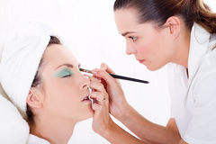 Make up artist. A pretty young make up artist doing a models eye makeup on white background stock photo