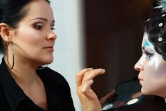 Make up artist. Creating art make up on model's face Stock Photography