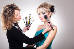 Make-up artist in action on beautiful doll face Royalty Free Stock Image