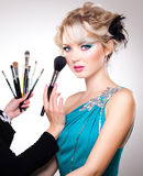 Make-up artist in action on beautiful doll face Stock Images