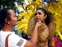 A make up artist applies make up to a parade participant in her colorful costume during the Sumaka Festival in Antipolo City. ANTIPOLO CITY, PHILIPPINES - MAY 1 royalty free stock photo