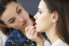 A make-up artist is applying makeup to a young girl. stock image