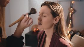 The make-up artist applies powder with a large brush to the face of a Caucasian blonde model. Makeup business woman. On. The background of garlands in stock video footage