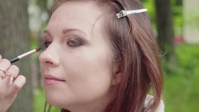Make up artist applies shades on girl`s eyelid before photoshoot stock video footage