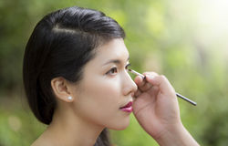 Make-up artist applying bright base color eyeshadow royalty free stock photography