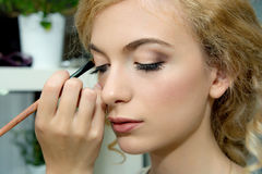 Make-up artist applying color eyeshadows on model's eye, close u Stock Photography