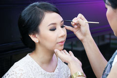 Make-up artist applying cosmetics on a beautiful y Stock Photography