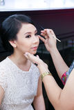 Make-up artist applying cosmetics on a beautiful y Stock Photos