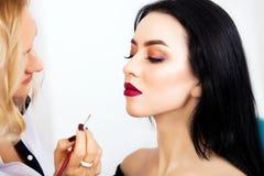 Make up artist applying eye shadow to a woman Stock Photo