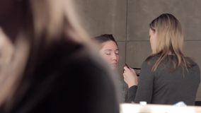 Make-up artist applying eye-shadows to model`s eyes stock video