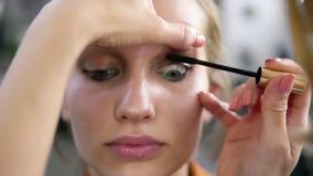 d33dac12283 Make-up artist applying eyelash makeup to blonde model`s eye. Close up view.