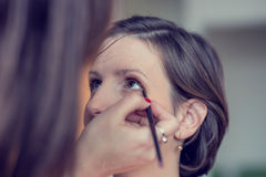 Make-up artist applying gentle makeup to a woman Royalty Free Stock Image