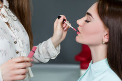 Make up artist applying gloss on woman lips. Make up artist applying gloss on women lips. Professional female beautician work with glamour attractive girl Stock Photo