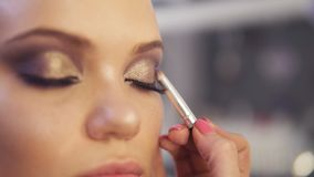 Make-up artist applying golden eye shadow makeup to the model`s eyes. Close up view.  stock video