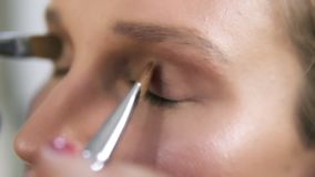 Make up artist applying light brown shadows on an eyelids with two brushes together, Close up of a young caucasian woman. `s eyes stock footage