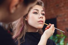 Applying lipgloss with a brush royalty free stock photography