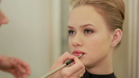 Make up artist applying lipstick with brush on pretty gorgeous woman lips. Closeup of visagiste and young girl. Beauty and makeup stock video