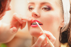 Make up artist applying lipstick with brush. Royalty Free Stock Images