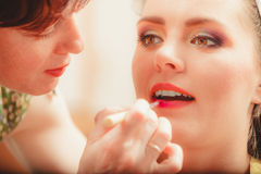 Make up artist applying lipstick with brush. Stock Photo