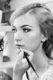 Make-up artist applying lipstick on model's lips Royalty Free Stock Photos