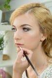 Make-up artist applying lipstick on model's lips Stock Image