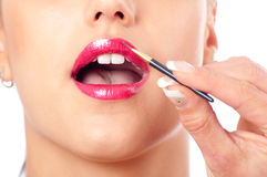 Make-up artist applying lipstick on mouth Stock Photo