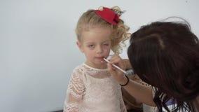 Make up artist applying lipstick to little pretty girl stock video footage