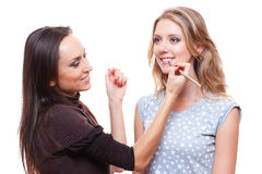 Make up artist applying lipstick to the model Stock Images