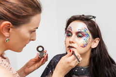 Make-up artist applying lipstick to model Royalty Free Stock Photography