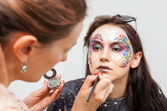 Make-up artist applying lipstick to model Stock Image