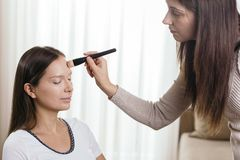 Make up artist blending face contours. Make up artist applying liquid face powder foundation to a female client`s face and blending contours royalty free stock photo
