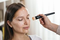 Make up artist applying liquid face powder. Foundation to a female client`s face with a make up brush royalty free stock images
