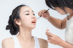 Make up artist applying make up to clean face a fashion model or bride Royalty Free Stock Photo