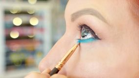 Make-up artist applying makeup to model`s eye. Close up view. royalty free stock images