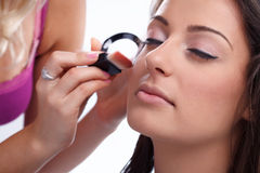 Make-up artist applying make-up on woman Stock Photos