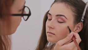 Make-up artist applying makeup on the face of the beautiful young sensual model stock video footage