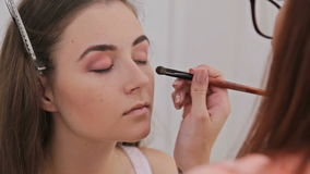 Make-up artist applying makeup on the face of the beautiful young sensual model stock footage