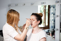Make-up artist applying makeup to a beautiful model Royalty Free Stock Photos