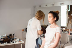 Make-up artist applying makeup to a beautiful model Royalty Free Stock Images